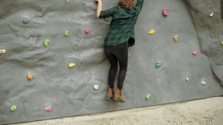 Girl climbing on the wall and smiling to the camera, steadycam shot