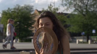 Girl covers her face with hat and smiling to the camera, steadycam shot, slow mo