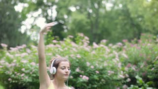 Girl doing exercises in the park and listening music on headphones, steadycam sh