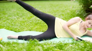 Girl doing exercises while lying on the mat and reading a book, steadycam shot