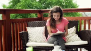 Girl doing homework on the deck and smiling to the camera