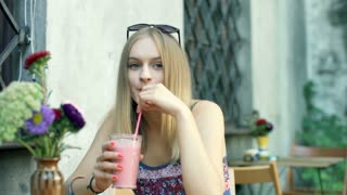 Girl drinking cocktail in the outdoor cafe and smiling to the camera