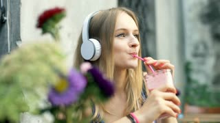 Girl drinking cocktail while relaxing in the outdoor cafe
