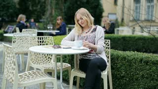 Girl drinking coffee and smiling to the camera in the outdoor cafe