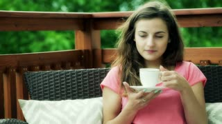 Girl drinking coffee and smiling to the camera on the deck