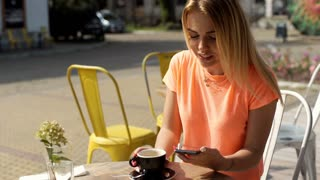 Girl drinking coffee and talking on loudspeaker while having a call, steadycam s