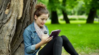 Girl drinking orange juice while browsing internet on tablet in the park