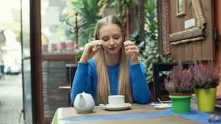 Girl drinking warming tea in the cafe and smiling to the camera