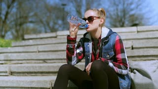 Girl drinking water on the stairs and relaxing