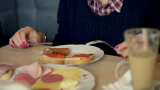Girl eating her breakfast and smiling to the camera, steadycam shot