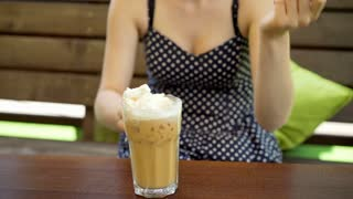 Girl eating whipped cream by using a straw from frappe