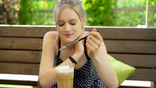 Girl eating whipped cream from a frappe and smiling to the camera