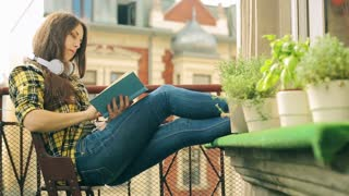 Girl finish reading book and start listening music on the balcony