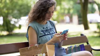 Girl finish texting on smartphone and leaving the bench in the park