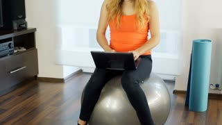 Girl finish using laptop and exercising on the ball, steadycam shot