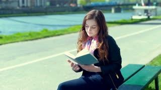 Girl finishes reading a book becuase he has a headache