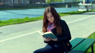 Girl finishes reading book and starts to relaxing on the bench