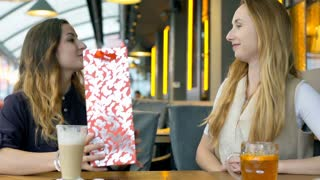 Girl giving present to her best friends in the cafe, steadycam shot