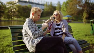 Girl gossiping on cellphone and boy using tablet in the park