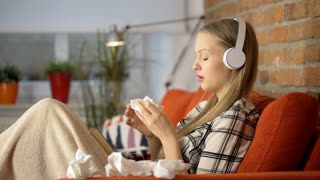 Girl has runny nose while being sick and listening music on headphones