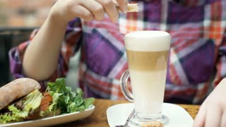 Girl having a healthy lunch in the cafe and adding sugar to the coffee
