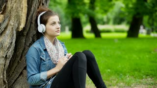 Girl having a painful headache while listening music in the park