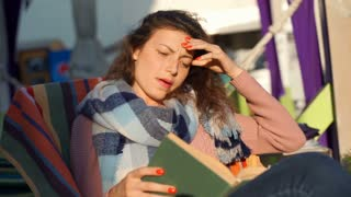 Girl having headache while reading book outdoors