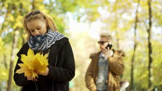 Girl holding bunch of maple leaves and her boyfriend talking on cellphone