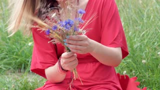 Girl holding field flowers while sitting on the grass in red dress