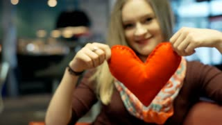 Girl holding handmade heart and showing it to the camera