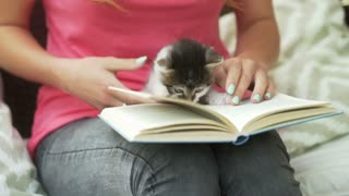Girl holding kitty on her knees and reading book