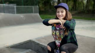 Girl holding skateboard and smiling to the camera
