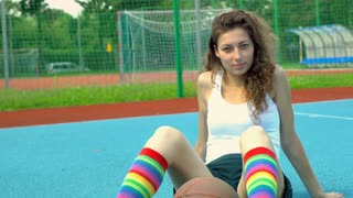 Girl in colorful socks sitting on the sports field and looking to the camera