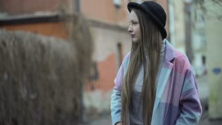 Girl in pastel jacket and black hat relaxing in the alley
