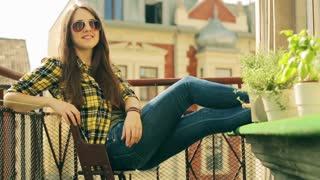 Girl in sunglasses smiling to the camera on the balcony, steadycam shot