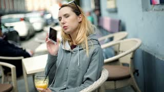 Girl in warm blouse looking worried while talking on cellphone