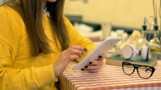 Girl in yellow jumper sitting by the table and using tablet steadycam shot