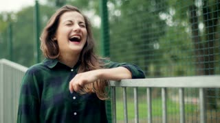 Girl leaning on fence and laughing to the camera