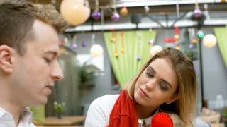 Girl listening her boyfriend on a date in the cafe, steadycam shot