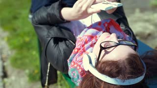 Girl listening music and browsing internet on smartphone while lying on the benc