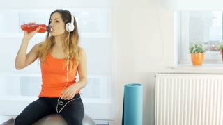Girl listening music and drinking energy drink while exercising on the ball, ste