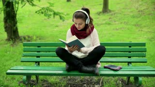 Girl listening music and reading book in the park