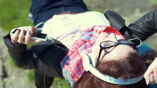 Girl listening music and yawning while lying on the bench