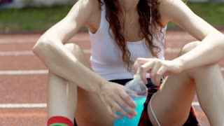 Girl listening music on headphones and drinking energy drink, steadycam shot