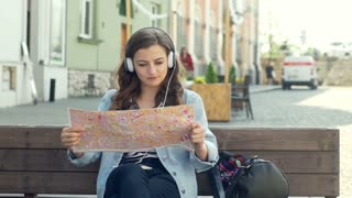 Girl listening music on headphones and reading map while sitting on the bench