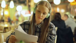 Girl listening music on headphones and reading papers in the cafe