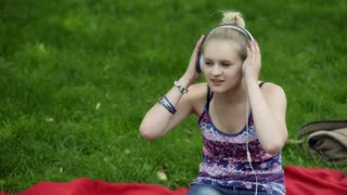 Girl listening music on headphones and relaxing in the park