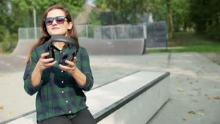 Girl listening music on headphones and smiling to the camera in skate park