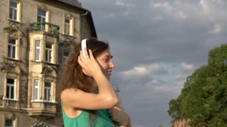 Girl listening music on headphones and smiling to the camera