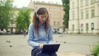 Girl listening music on heaphones and using laptop while sitting on the square